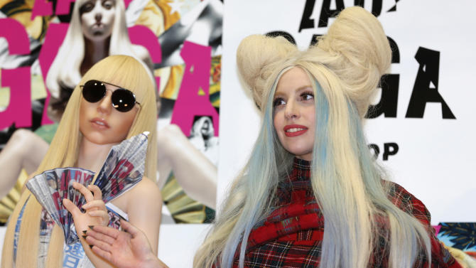 "Lady Gaga poses for photographers with her life-sized doll during a press conference to promote her album ""ARTPOP"" in Tokyo, Sunday, Dec. 1, 2013. (AP Photo/Shizuo Kambayashi)"