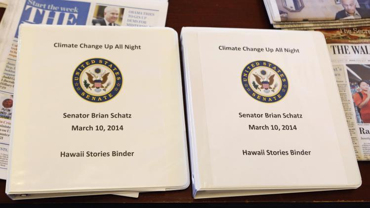 Binders of Senator Brian Schatz (D-HI) are seen before the Senate Climate Action Task Force meeting
