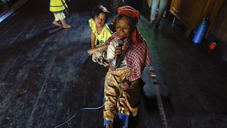 An ethnic Kayan woman sings karaoke in her home in Panpet village, Demoso township Kayah state