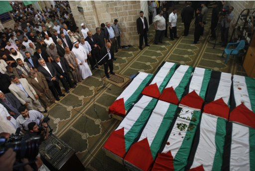 Palestinians pray next to flag-covered coffins containing the remains of Palestinian militants in Gaza City