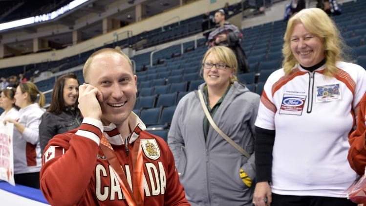 Skip Jacobs talks to his father on the phone after he defeated Team Morris during the men's final at the Roar of the Rings Canadian Olympic Curling Trials in Winnipeg