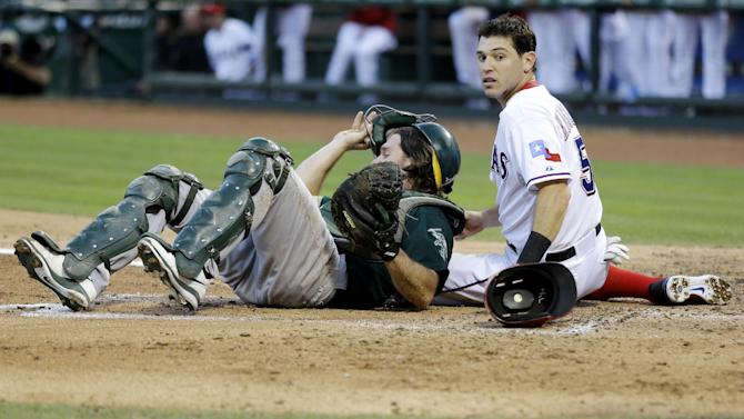 Texas Rangers' Ian Kinsler looks back to see the ball as Oakland Athletics catcher John Jaso recovers from a collision with Kinsler in the third inning of a baseball game Tuesday, June 18, 2013, in Arlington, Texas. Kinsler was safe on the A.J. Pierzynski single. (AP Photo/Tony Gutierrez)