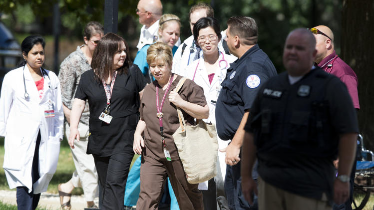 Hospital workers leave the scene of a shooting Thursday