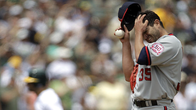 Los Angeles Angels' Joel Pineiro, right, wipes his face after giving up a grand slam to Oakland Athletics' Conor Jackson, running bases left, in the first inning Sunday, July 17, 2011, in Oakland, Calif. (AP Photo/Ben Margot)