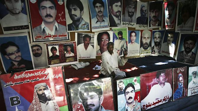 "In this Monday, May 6, 2013 photo, Abdul Qadeer Rehki who lost his son, sits among posters with photos of other missing people in Quetta, Pakistan. The graffiti on walls around this Pakistani provincial capital hold a dire warning ahead of this weekend's national elections, ""Voting means death."" It's a very real threat: Over recent weeks at least six people have been killed and nearly 40 wounded in bombings and grenade attacks targeting candidates. (AP Photo/Arshad Butt)"