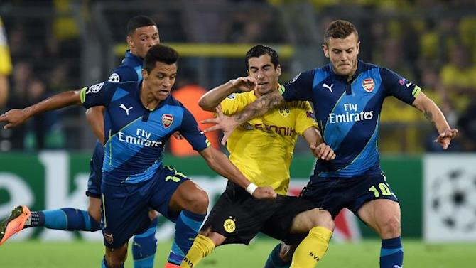 Arsenal midfielder Jack Wilshere (R) and striker Alexis Sanchez (L) tackle Dortmund midfielder Henrikh Mkhitaryan (C) during the Champions League Group D first leg in Dortmund, Germany on September 16, 2014