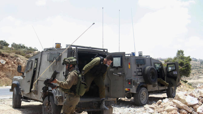 Israeli soldiers deploy near the West Bank city of Hebron, Friday, June 13, 2014. Israeli soldiers searched the West Bank on Friday for three missing teenagers from nearby settlements, one of them a U.S. citizen, amid fears Palestinian militants abducted them, authorities said. (AP Photo/Nasser Shiyoukhi)