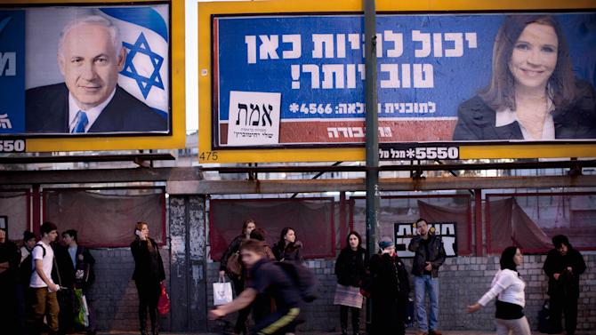 """Israelis wait for transportation under election campaign billboards of Israeli Prime Minister and Likud Party leader Benjamin Netanyahu, left, and Israel's Labor party candidate Shelly Yachimovichin, in the central Israeli city of Ramat gan, Monday, Jan. 21, 2013. The general elections will be held on Tuesday, Jan. 22, 2013. Hebrew on billboard reads, """"It can be better here."""" (AP Photo/Oded Balilty)"""