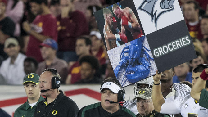 Oregon head coach Chip Kelly, center, watches from the sideline as a play card is held behind him during the second half of an NCAA college football game against Southern California, Saturday, Nov. 3, 2012, in Los Angeles. Oregon won 62-51. (AP Photo/Bret Hartman)
