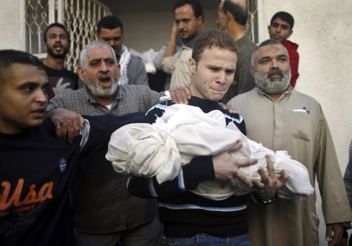 Jihad al-Masharawi, a Palestinian employee of BBC Arabic in Gaza, carries the body of his son Omar, who according to hospital officials was killed by an Israeli air strike in Gaza City