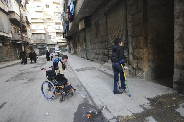 Disabled 11-year-old boy Abdel Jaleel al-Homsy walks with crutches towards his home as he is helped by his friend Mohamad Qanawati in Aleppo's Bustan al-Qasr