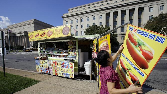 Cathy Vu, from Annandale, Va., packs up her truck on Constitution Avenue across the street from the National Archives, behind left, and Federal Trade Commission (FTC) behind right, Friday, Oct. 4, 2013, in Washington. Vu said today is the only day this week she has come out with the truck, and that business has been bad, since the federal government shutdown started Tuesday. (AP Photo/Alex Brandon)