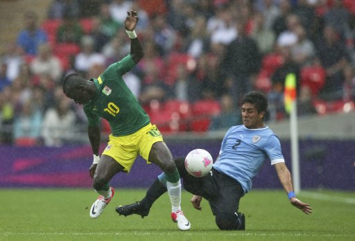 Senegal's Sadio Mane competes for possession with Uruguay's Ramon Arias during their men's preliminary first round Group A soccer match at the London 2012 Olympic Games in the Wembley Stadium in London