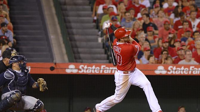 Los Angeles Angels' C.J. Cron, right, hits a three-run home run as Seattle Mariners catcher Jesus Sucre looks on during the seventh inning of a baseball game, Wednesday Sept. 17, 2014, in Anaheim, Calif. (AP Photo/Mark J. Terrill)