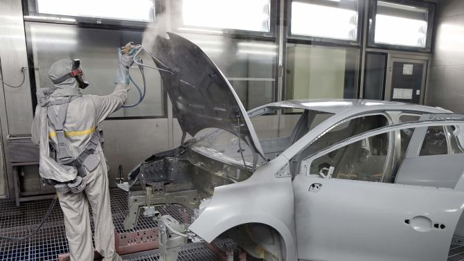 An employee works on the automobile assembly line of a Renault Clio IV at the Renault automobile factory in Flins