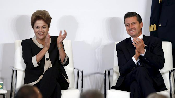 Mexico's President Enrique Pena Nieto smiles with Brazil's President Dilma Rousseff as they applaud during the business seminar Mexico-Brazil in Mexico City