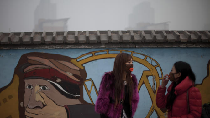 In this Jan. 12, 2013 photo, a woman adjusts her mask while walking with her friend outside an amusement park on a polluted day in Beijing, China. Facing public outrage over smog-choked cities and filthy rivers, China's leaders are promising to clean up its neglected environment, a pledge that sets up a clash with political pressures to keep economic growth strong. (AP Photo/Alexander F. Yuan)