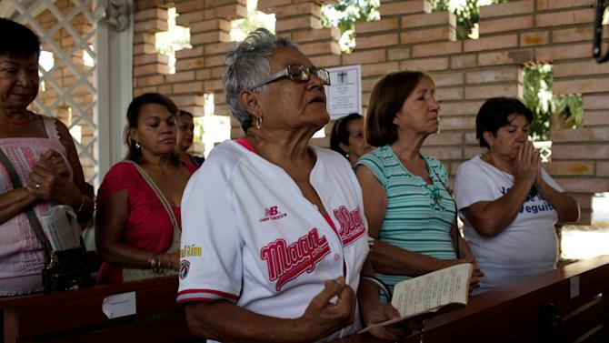 """Supporters of Venezuela's President Hugo Chavez pray for the ailing president at the military hospital's chapel in Caracas, Venezuela, Tuesday, March 5, 2013. A brief statement read on national television by Communications Minister Ernesto Villegas late Monday carried the sobering news about the charismatic 58-year-old leader's deteriorating health. Villegas said Chavez is suffering from """"a new, severe infection."""" The state news agency identified it as respiratory. (AP Photo/Ariana Cubillos)"""