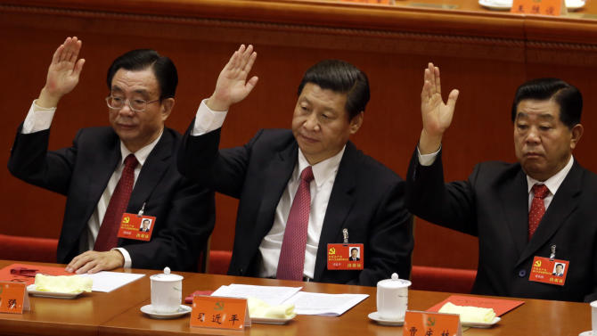 Chinese vice President Xi Jinping, center, Central Commission for Discipline Inspection head He Guoqiang, left, and Chinese People's Political Consultative Conference Chairman Jia Qinglin raise their hands to show approval for a work report during the closing ceremony for the 18th Communist Party Congress held at the Great Hall of the People in Beijing, China, Wednesday Nov. 14, 2012. (AP Photo/Lee Jin-man)