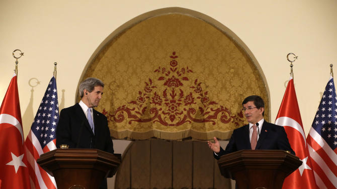 U.S. Secretary of State John Kerry, left, listens as Turkish Foreign Minister Ahmet Davutoglu speaks during a news conference at Ankara Palace in Ankara, Turkey, on Friday, March 1, 2013. Ankara is the fifth leg of Kerry's first official overseas trip, a nine-day dash through Europe and the Middle East. (AP Photo/Jacquelyn Martin, Pool)