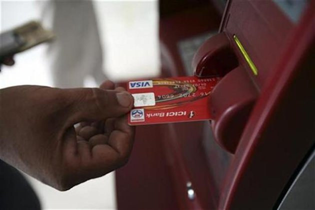A customer uses his card to withdraw money from an ATM in Jammu October 14, 2008. REUTERS/Amit Gupta /Files