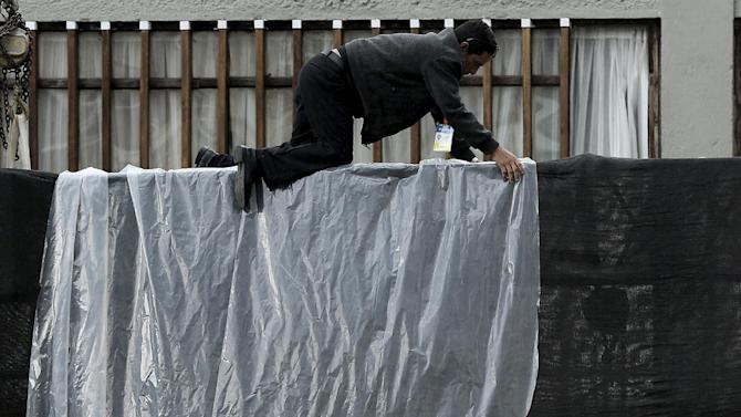 A worker covers a big screen as Pope Francis attends a meeting at the Catholic University in Quito