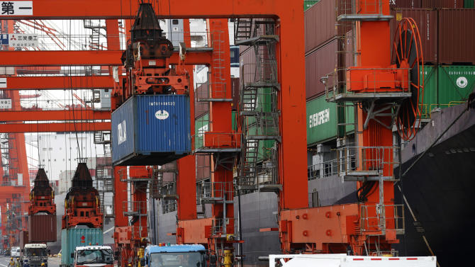 Workers watch shipping and discharging of containers at a port in Tokyo, Wednesday, June 19, 2013. Japan's trade deficit rose nearly 10 percent in May to 993.9 billion yen (nearly $10.5 billion) as rising costs for imports due to the cheaper yen matched a rebound in exports. (AP Photo/Shizuo Kambayashi)