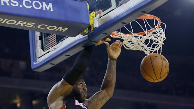 Miami Heat's LeBron James, left, dunks next to Golden State Warriors' Harrison Barnes (40) during the first half of an NBA basketball game in Oakland, Calif., Wednesday, Jan. 16, 2013. (AP Photo/Marcio Jose Sanchez)