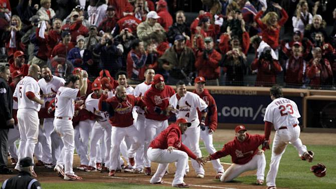St. Louis Cardinals greet David Freese, right, at home after Freese hit a solo home run off a pitch by Texas Rangers' Mark Lowe in the 11th inning to win Game 6 of baseball's World Series 10-9, Thursday, Oct. 27, 2011, in St. Louis. The series is tied 3-3. (AP Photo/Jeff Roberson)