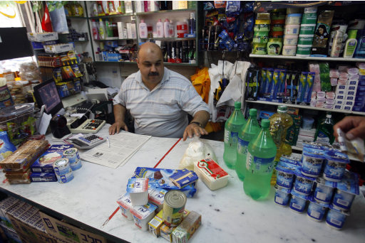 In this Monday, July  4, 2011 photo, Maher Khoudari, owner of a grocery shop, sits behind the counter of his store in Gaza city. Maher Khoudari boasts that his Gaza grocery has a wide assortment of chocolates for sale _ even some you couldn't find in the cosmopolitan Israeli city of Tel Aviv. The problem is, there is no one to buy them. Israel eased its blockade of the Hamas-ruled Palestinian territory a year ago and now allows virtually all consumer goods in, meaning there are no longer acute shortages of foods or basic household items. Tiny construction projects have begun sprouting up, and Gaza is awash in big ticket items such as cars and refrigerators. But deep troubles remain. Israel maintains restrictions on the key construction and export sectors, and the vast majority of Gazans are still barred from traveling in and out of the territory. Nearly half the work force is unemployed, and more than 70 percent of the population relies on food handouts, making fancy chocolates, like any other non-essential goods, a luxury most cannot afford. (AP Photo/Hatem Moussa)