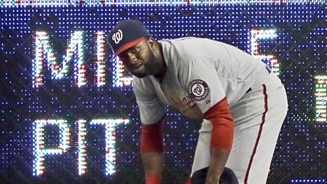 Washington Nationals right fielder Byrce Harper lies on the field as center fielder Denard Span looks over him after Harper hit the wall chasing a triple off the Los Angeles Dodgers' A.J. Ellis in the fifth inning of a baseball game in Los Angeles Monday, May 13, 2013. (AP Photo/Reed Saxon)