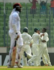 Bangladesh's Sohag Gazi (R) celebrates with teammates after the dismissal of West Indies cricketer Chris Gayle (L) during the first day of their first Test in Dhaka. The off-spinner opened the bowling attack and dismissed Gayle (24) and Darren Bravo (14) in his first spell