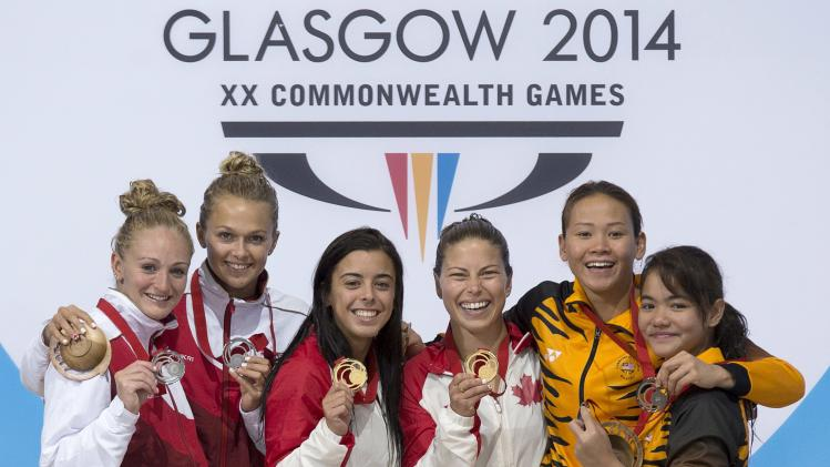 England's silver medallists Sarah Barrow and Tonia Couch, left, Canada's gold medallists Meaghan Benfeito, center left, and Roseline Filion, along with Malaysia's bronze medallists Pandelela Rinong Pamg and Nur Dhabitah Sabri, right, stand on the podium after the women's synchronized 10-meter platform event at the Commonwealth Games in Edinburgh, Scotland on Wednesday, July 30, 2014. (AP Photo/The Canadian Press, Andrew Vaughan)