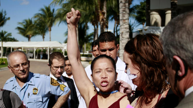 An activists gestures while UN security agents escort fellow activists outside the main facility where the UN Climate Change Conference is being held after they entered the site protesting against the event in Cancun, Mexico, Friday, Dec. 10, 2010. (AP Photo/Israel Leal)