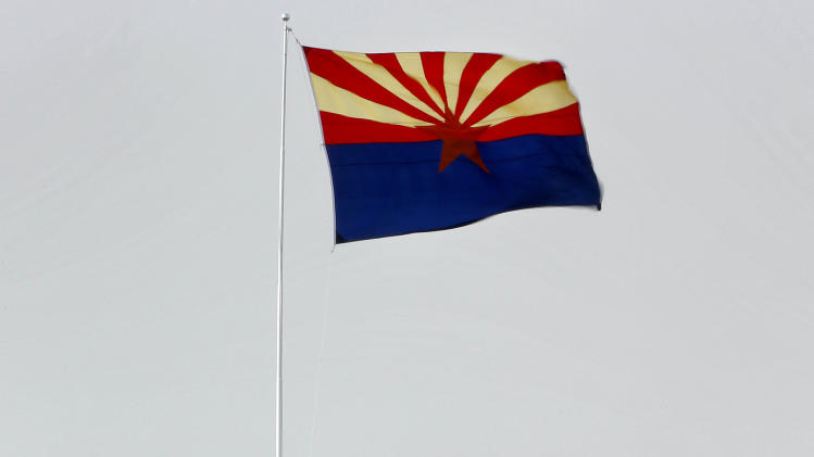 High winds stretch palm trees and the Arizona state flag, Monday, April 8, 2013 in Chandler, Ariz. The National Weather Service has issued high wind and blowing dust advisories with wind gusts as high as 60 mph this afternoon and into the early evening. (AP Photo/Matt York)