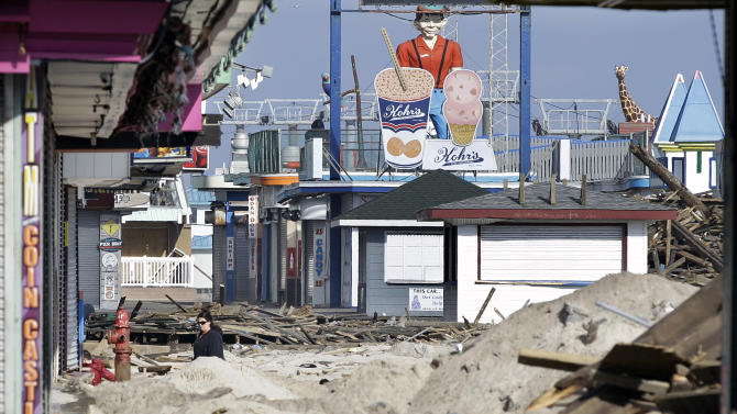 FILE - In this Nov. 22, 2012 file photo, a woman walks past debris from the damaged boardwalk in Seaside Heights, N.J.  Heavy equipment including a gigantic drill and a pile-driving machine were brought onto the sand in the south end of town Friday, Feb. 15, 2013, as workers began drilling holes in the sand and pounding wooden pilings into them, shaking the ground for blocks around. It marked the beginning of a $3.6 million contract the borough awarded to rebuild the boardwalk. Mayor William Akers said the initial work, restoring the boardwalk so that it can be walked on safely, should be done by May 10. Railings, lighting and ramps will be part of a second contract that has yet to be awarded. The project is also likely to include a protective seawall, and cost between $6 million and $7 million, the mayor said. (AP Photo/Mel Evans, File)