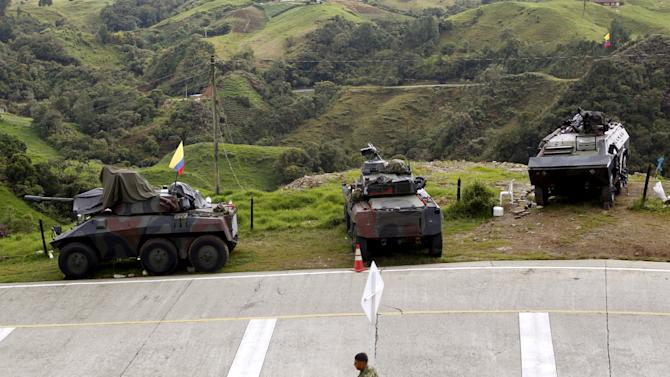 Armored army vehicles are seen on guard along a road close to a zone of landmines planted by rebels groups near Sonson in Antioquia province