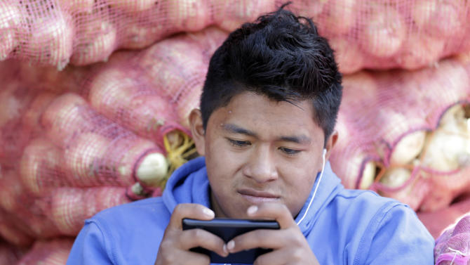 In this Aug. 24, 2014, photo, a young man texts a message on his mobile phone while working at the Mayorista Market in Quito, Ecuador. Ecuador's Central Bank is getting ready to use electronic currency in which consumers will initially be able to use it to make and receive payments using their cellphones. Ecuador is heralding its plans to create the world's first government-issued digital currency, which some analysts believe could ultimately replace the country's existing currency, the U.S. dollar, which the government cannot control. (AP Photo/Dolores Ochoa)