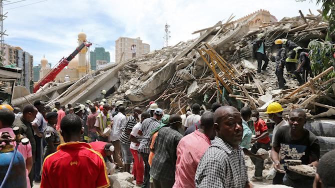 In this photo released by China's Xinhua News Agency, rescue workers remove debris at the site of a building collapse site in downtown Dar es Salaam, Tanzania, Friday, March 29, 2013. A Tanzanian police official said two people have died after the building under construction collapsed in the country's largest city and economic center. (AP Photo/Xinhua, Zhang Ping) NO SALES