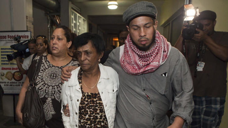 "Maria Matias, center, mother of former world boxing champion Hector ""Macho"" Camacho, and her grandson Hector Jr. walk together after holding a news conference at Centro Medico trauma center in San Juan, Puerto Rico, Friday, Nov. 23, 2012. Camacho, who has been unconscious since he was shot in the face last Tuesday and declared brain dead by doctors, will be taken off life support on Saturday, his mother said in the brief news conference, a decision that her grandson, Hector Jr. opposes. (AP Photo/Dennis M. Rivera Pichardo)"
