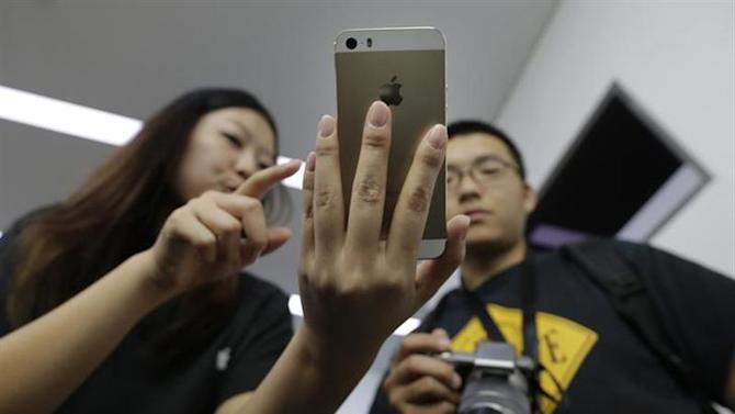 A staff member shows the new iPhone 5S Touch ID fingerprint recognition feature to a journalist at Apple Inc's announcement event in Beijing, September 11, 2013. REUTERS/Jason Lee