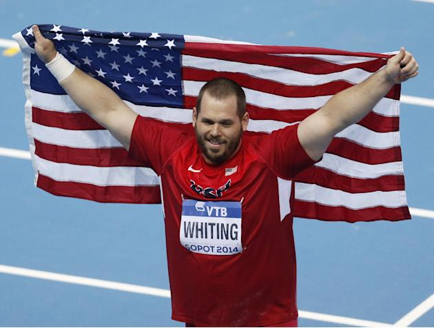 United States' Ryan Whiting carries the US flag after winning the shot put final during the Athletics World Indoor Championships in Sopot, Poland, Friday, March 7, 2014