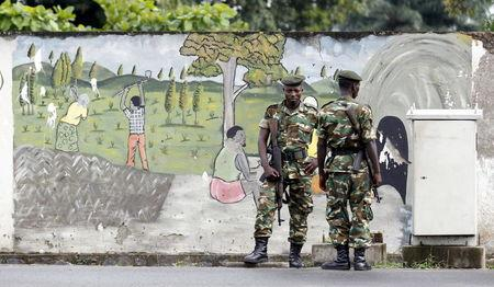 Military officers stand guard near a wall mural showing people working in farms following recent clashes between protesters and riot police as it is used to block a main street in Burundi's capital Bujumbura