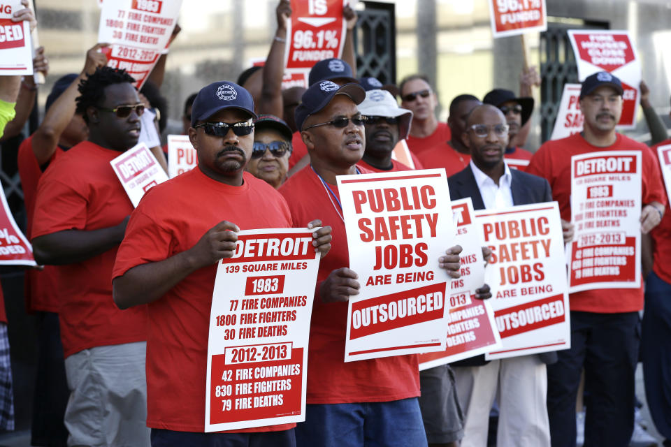 Firefighters protest outside the Theodore Levin United States Courthouse, in Detroit, Wednesday, July 24, 2013. Detroit's bankruptcy is hitting a courtroom for the first time as a judge considers what to do with challenges from retirees who claim their pensions are protected by the Michigan Constitution. (AP Photo/Paul Sancya)