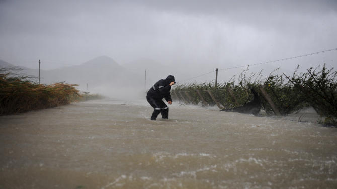 A farmer battling the storm as he wade through a flooded road in Hepu township, Xiangshan county in east China's Zhejiang province, Wednesday Aug. 8, 2012. Typhoon Haikui slammed into eastern China's Zhejiang province early Wednesday, packing winds up to 150 kilometers (90 miles) per hour and triggering flooding. (AP Photo) CHINA OUT