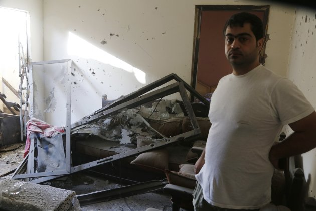 A man stands in his damaged house after two rockets hit houses and a car sales yard in Beirut suburbs