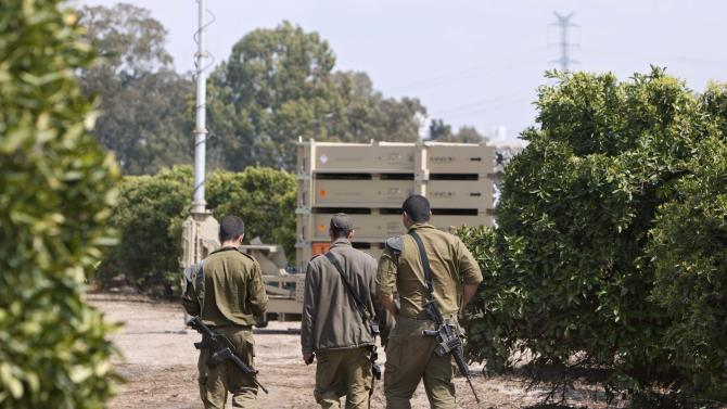 "This photo taken Tuesday, March 27, 2012 shows Israeli soldiers walk past an Iron Dome short-range rocket interceptor battery, deployed in central Israel. The Pentagon says it will ask Congress for more money for Israel's anti-rocket system known as the ""Iron Dome."" (AP Photo/Oded Balilty)"