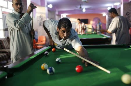 File photo of Iraqi Shi'ite men playing pool in Sadr City in Baghdad