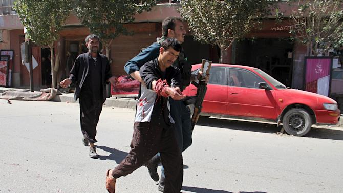 Afghan policeman helps a wounded man after an explosion in Ghazni city