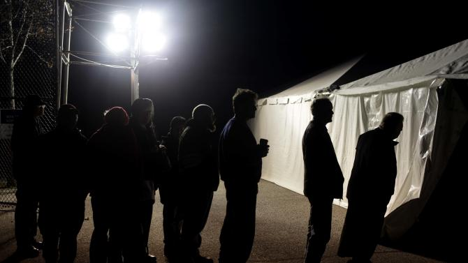 Under the lights of a generator, voters wait in line outside of a tent serving as a polling site in the Midland Beach section of Staten Island, New York, on Election Day Tuesday, Nov. 6, 2012. The original polling site, a school, was damaged by Superstorm Sandy. (AP Photo/Seth Wenig)